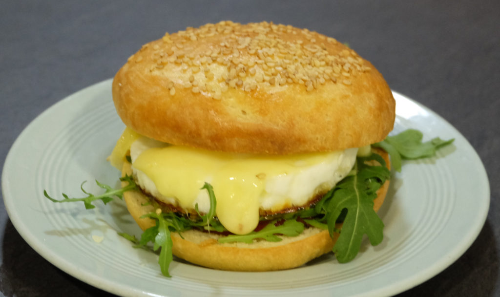 A bun with rocket, red onion chutney, fired egg and cheddar